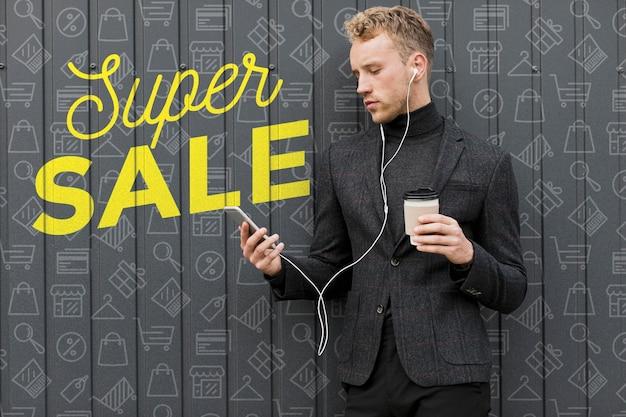 若い男が一杯のコーヒーを保持していると携帯電話を見て