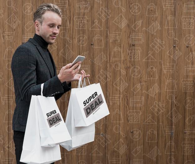 電話をチェックする買い物袋を持つ男