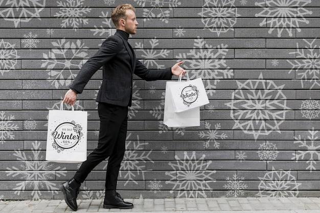買い物袋と歩く若い男