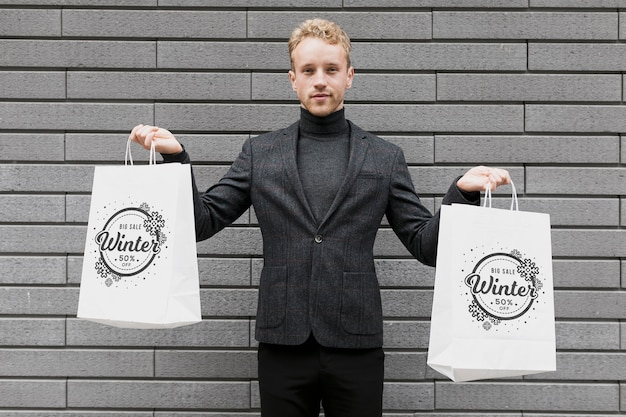 Мужчина держит в каждой руке хозяйственные сумки