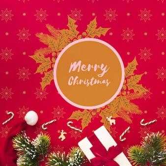 クリスマスの赤い背景に落葉性の葉とメリークリスマス