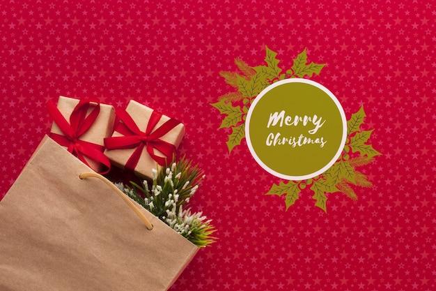 Бумажный пакет, полный подарков на красном фоне рождество