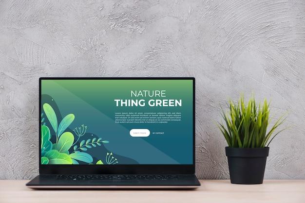 オフィスの机の上の植物の横にあるノートパソコン