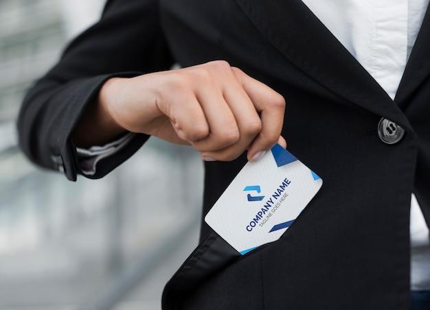 ポケットから訪問カードのモックアップを出してビジネス女性