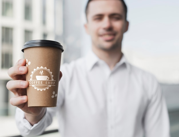 コーヒーカップのモックアップを保持しているビジネスの男性
