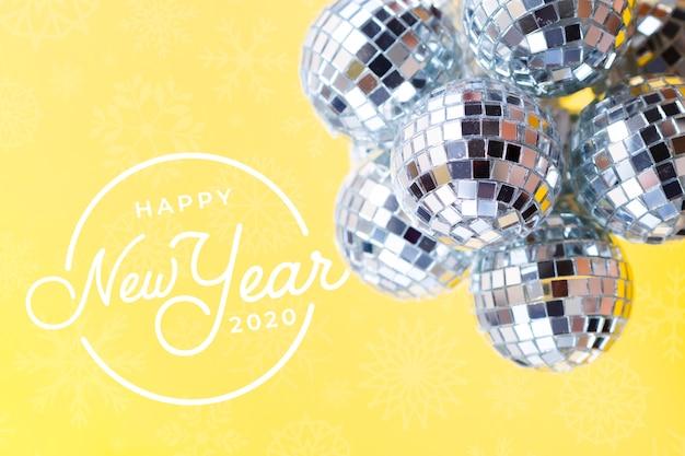新年の黄色の背景に銀のクリスマスボールの山