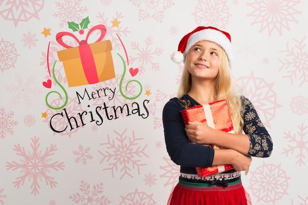 Молодая девушка в новогодней шапке держит подарок