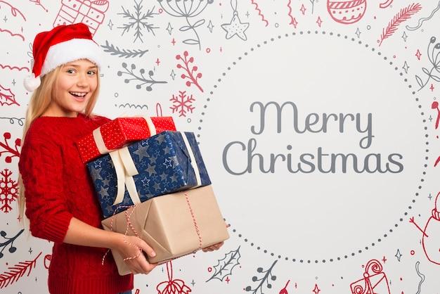 クリスマスの贈り物のスタックを保持している幸せな女の子