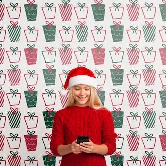 Макет молодой девушки, глядя на мобильный
