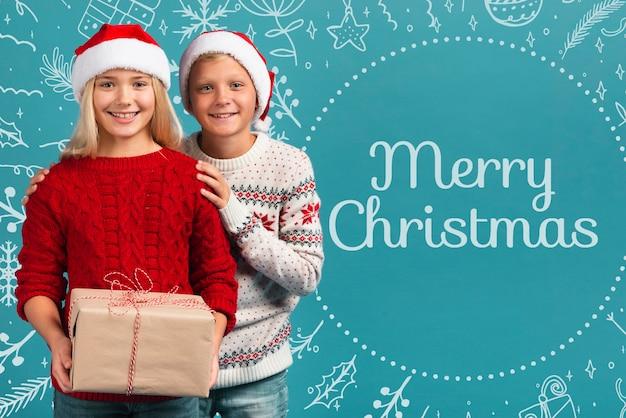 Молодые братья и сестры, держа подарок на рождество