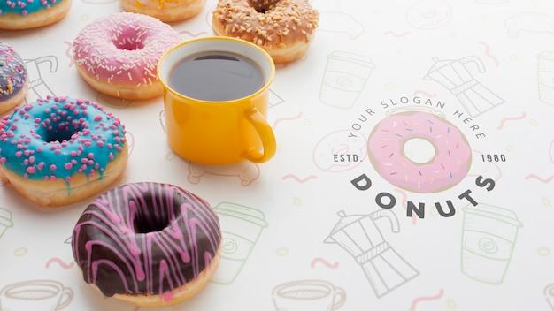 Композиция из разноцветных пончиков и черного кофе с макетом