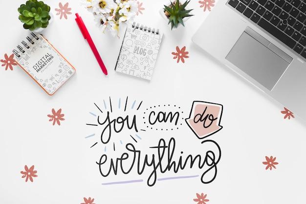 ラップトップノートと白い机の上のやる気を起こさせるメッセージ