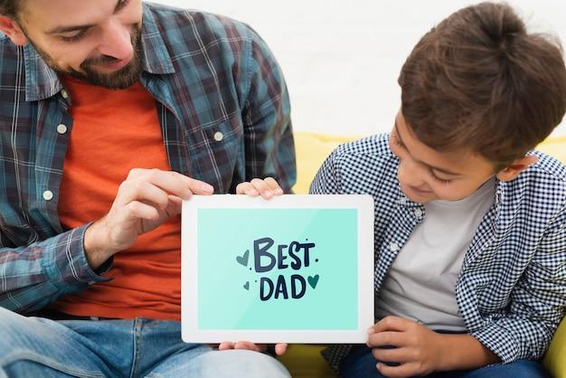 お父さんと息子の電子タブレットを保持