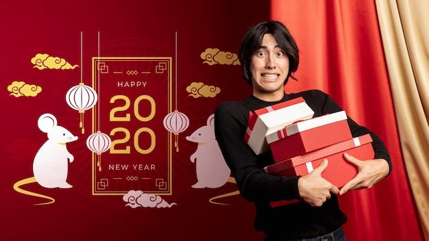 Мужчина держит подарочные коробки на новый год