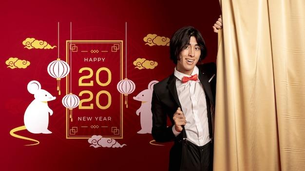 新年の装飾の横に立っている男