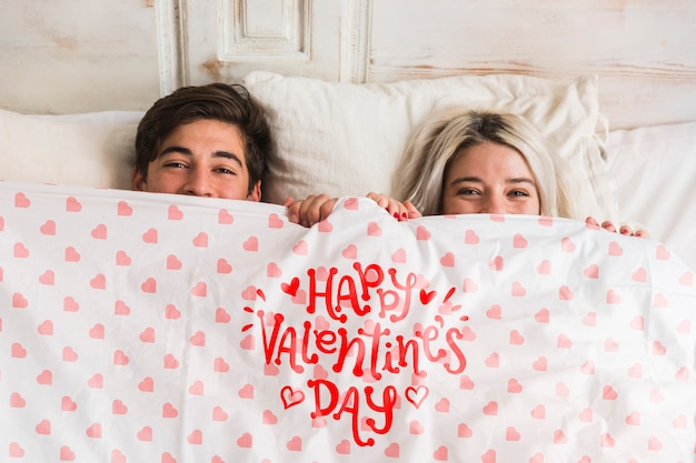 バレンタインデーのためのベッドでかわいい若いカップル