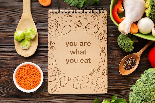 ノートブックの横にあるテーブルの上の野菜