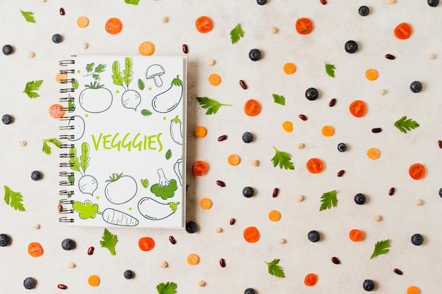 ノートブックモックアップとフラットレイアウト野菜盛り合わせ