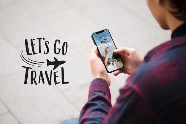 旅行に行き、肩越しに携帯電話を見ている男
