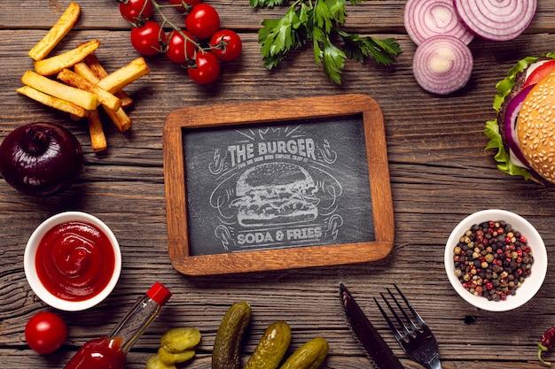 ハンバーガーと食材の木製の背景に囲まれたモックアップフレーム