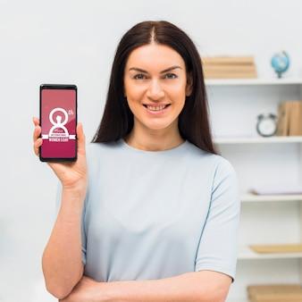 電話のモックアップを持つミディアムショット女性