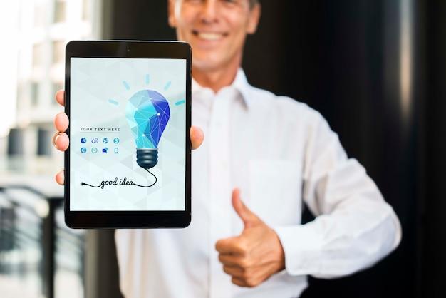 Смайлик бизнесмен на открытом воздухе держит вертикальный цифровой планшет