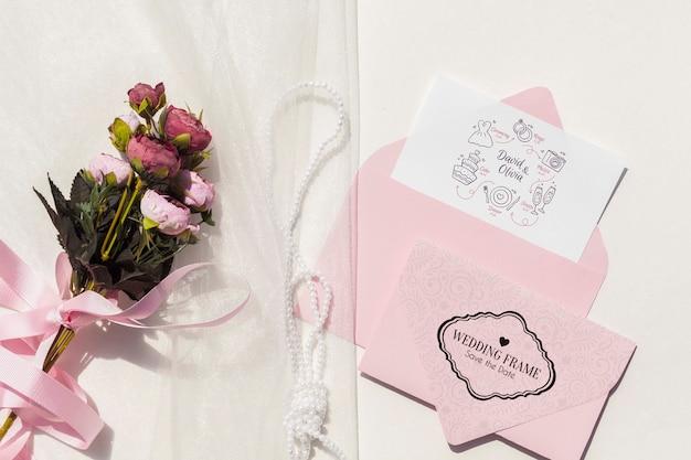 封筒と花の花束とフラットレイアウトの結婚式のアイデア