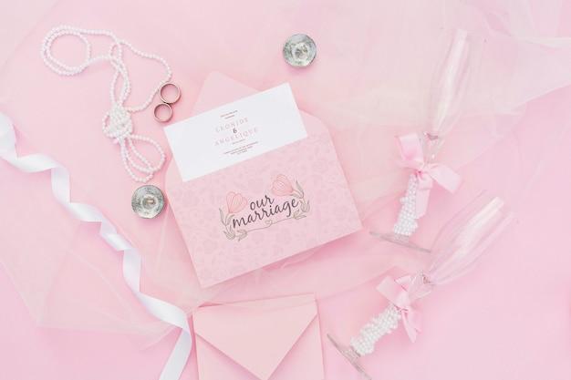 封筒とグラスシャンパンとピンクの色調の結婚式の装飾