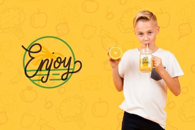 オレンジジュースを飲む子供の正面図