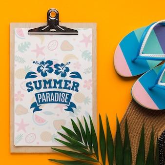 夏の楽園のクリップボードとフリップフロップのトップビュー