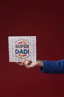 Рука держит картонный макет на бордовом фоне