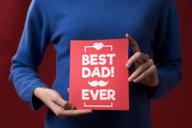 Дочь держит картонный макет на бордовом фоне