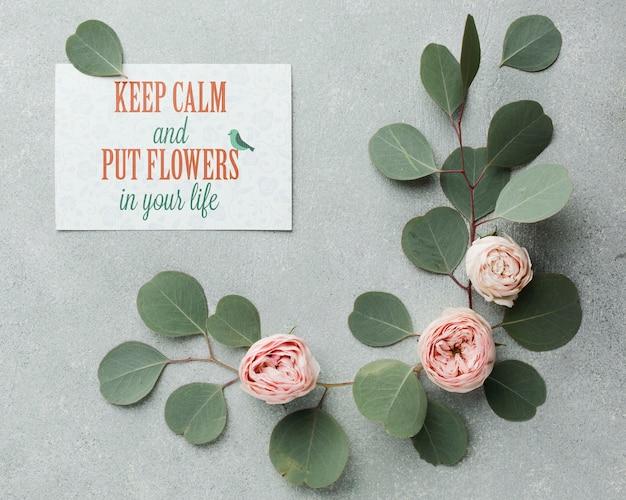 葉とカードで柔らかいバラのトップビュー