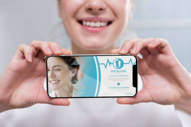 Крупным планом стоматолог, держа смартфон макет