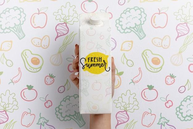 Рука держит коробку молока с макетом