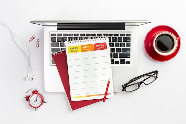 Еженедельный планировщик сверху ноутбука с кофе