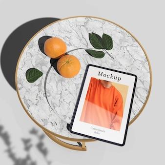 Высокий угол планшета на столе с апельсинами и листьями
