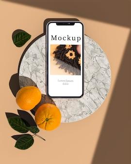 Смартфон с цитрусовыми и листьями