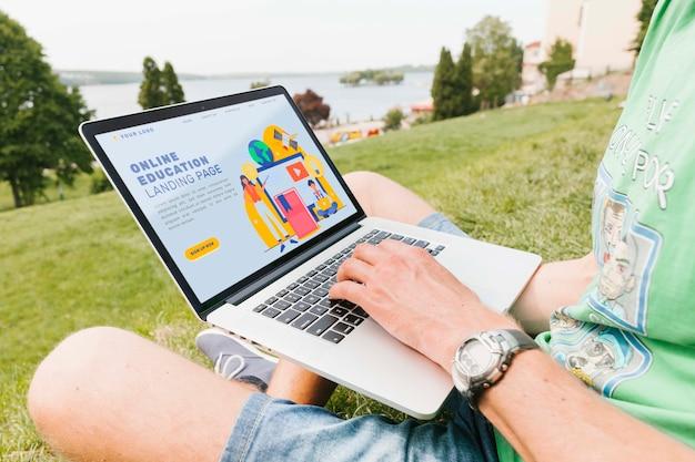 Крупным планом мужчина работает на ноутбуке на открытом воздухе