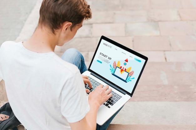 Молодой студент работает на ноутбуке на открытом воздухе