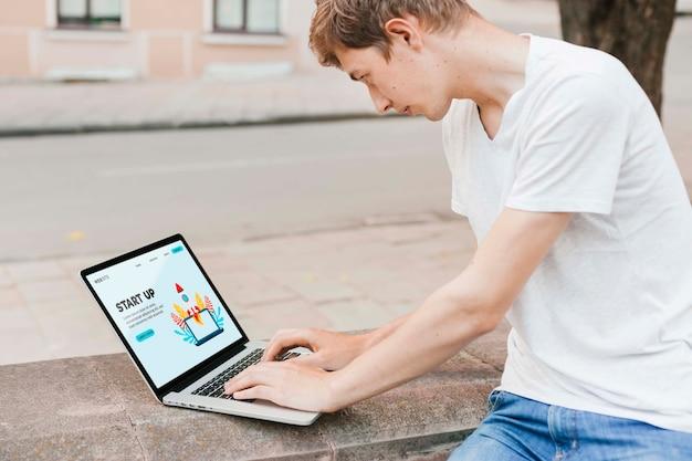 Студент работает на ноутбуке на открытом воздухе