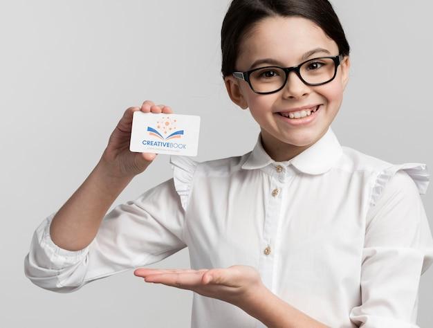 Молодая девушка держит макет визитной карточки