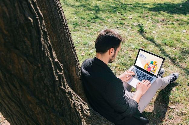 ノートパソコンで作業するフルショット男