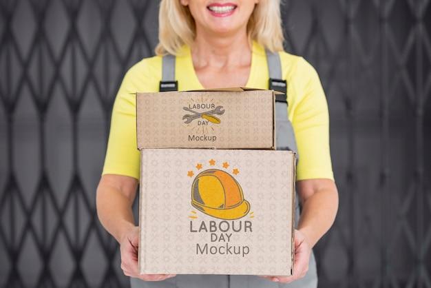 Работник женщина, держащая макет коробки