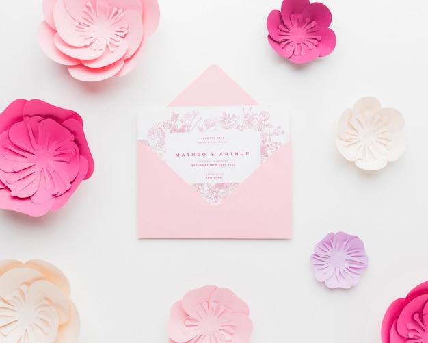 白い壁紙に紙の花と結婚式の招待状のモックアップ