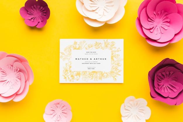 黄色の背景に紙の花と結婚式の招待状のモックアップ