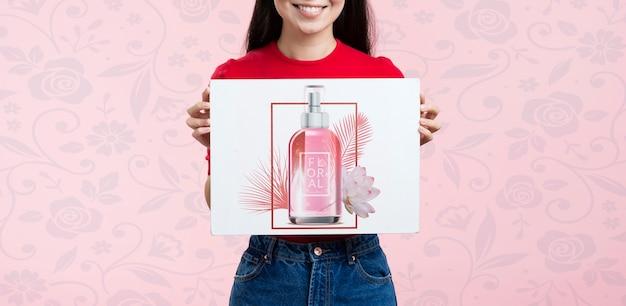 Женщина вид спереди держит макет рекламы для косметики