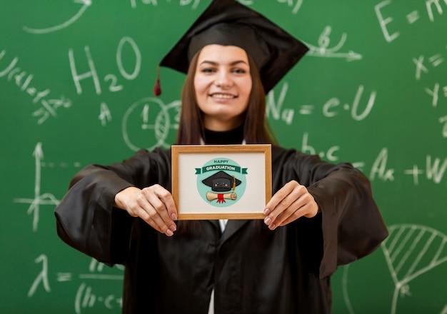 卒業証書を保持している肯定的な若い女の子