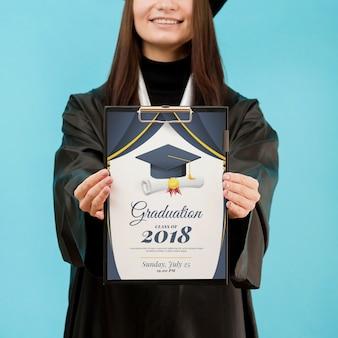 若い学生のモックアップで卒業証書を保持