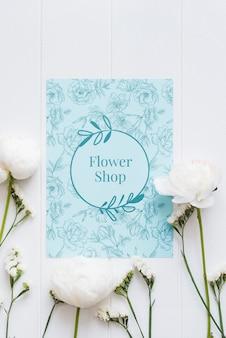 青いフラワーショップのモックアップと白い花